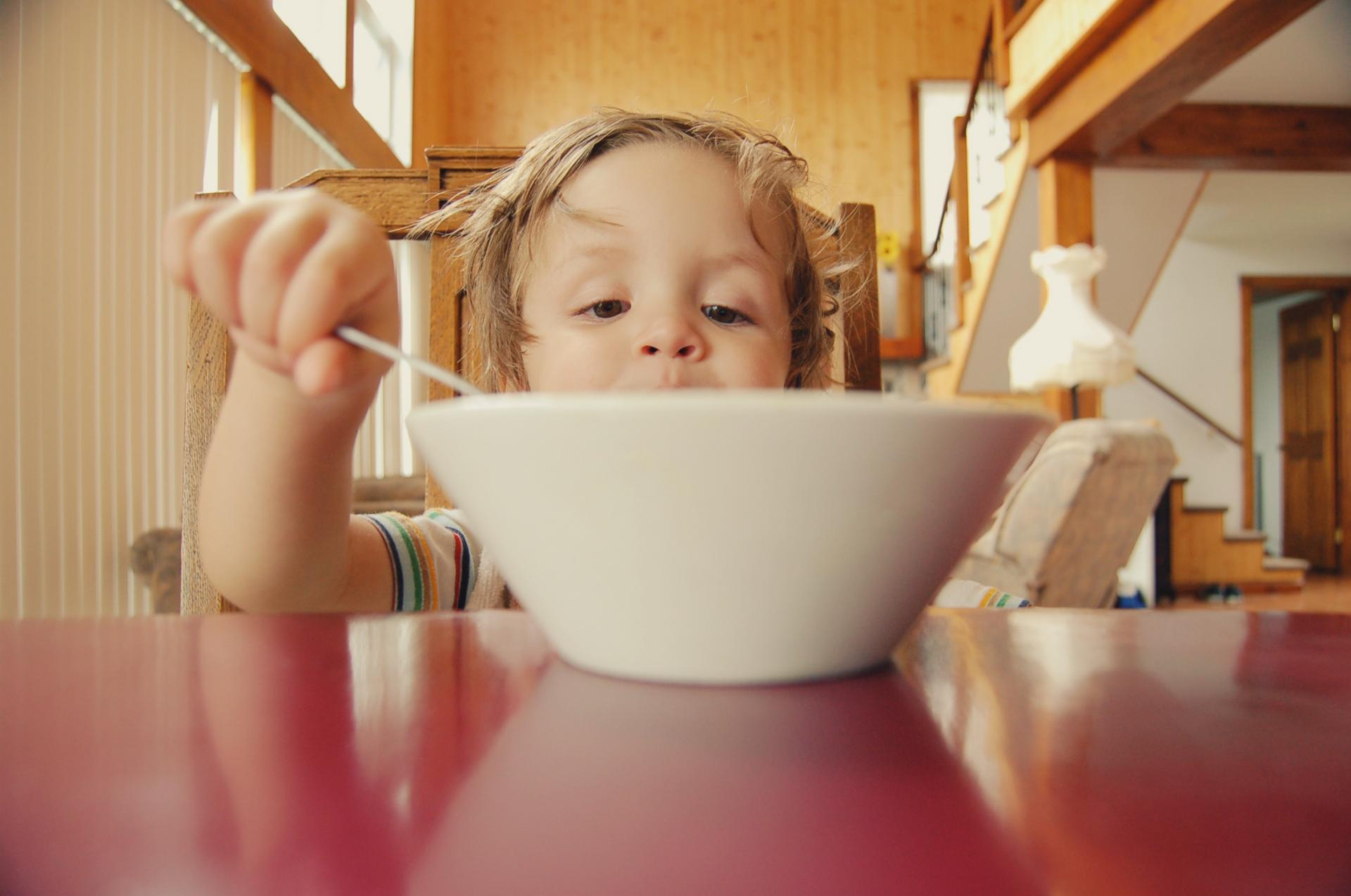child eating food from a bowl